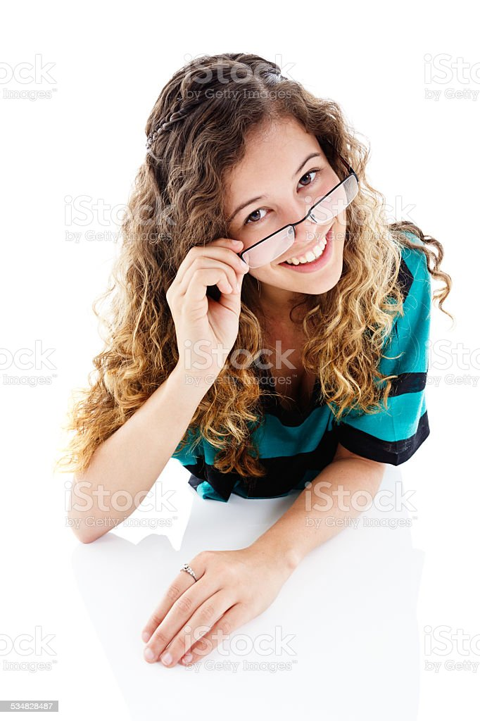 Looking down at pretty woman smiling over her glasses stock photo
