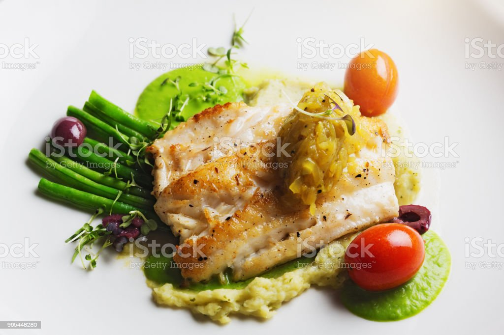 Looking down at restaurant dish of grilled fish with accompaniments zbiór zdjęć royalty-free