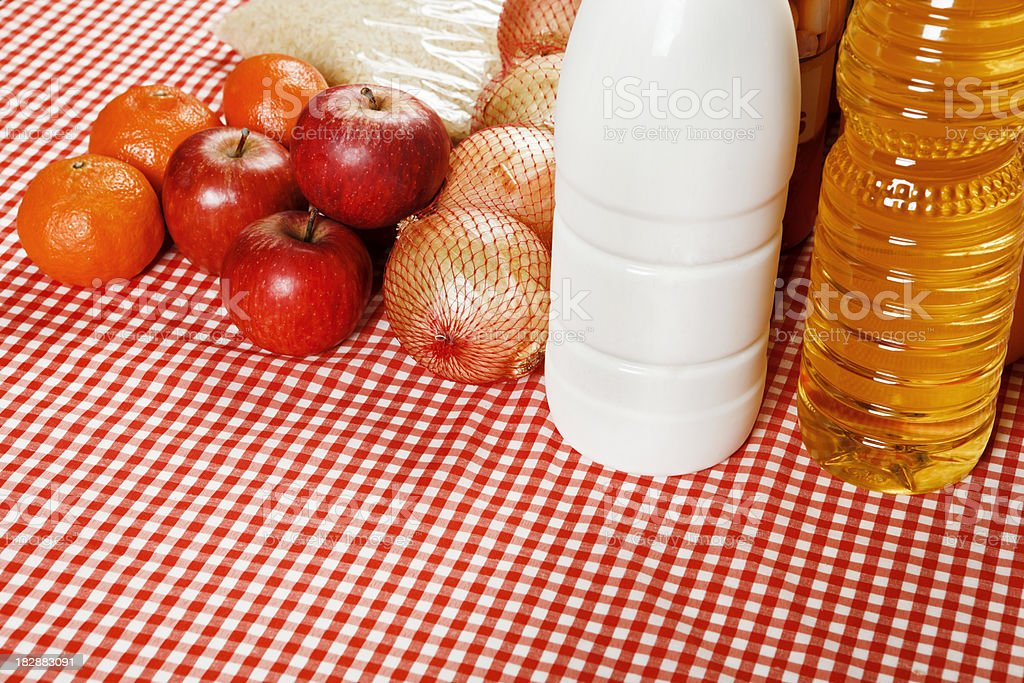 Looking down at selection of basic foods on gingham tablecloth stock photo