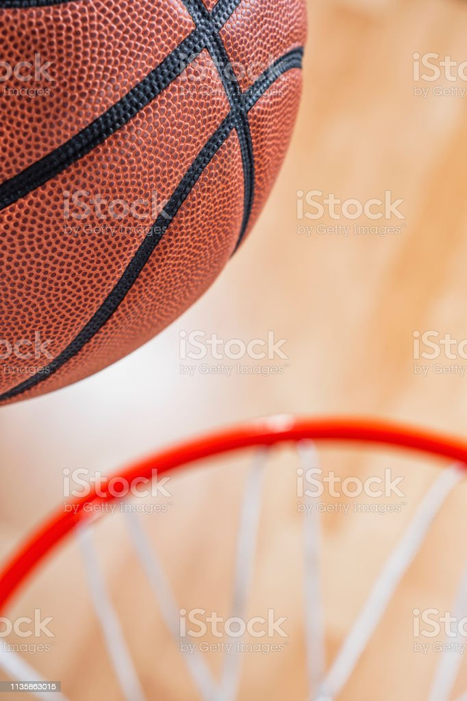 A close-up view looking down at an orange basketball almost going...
