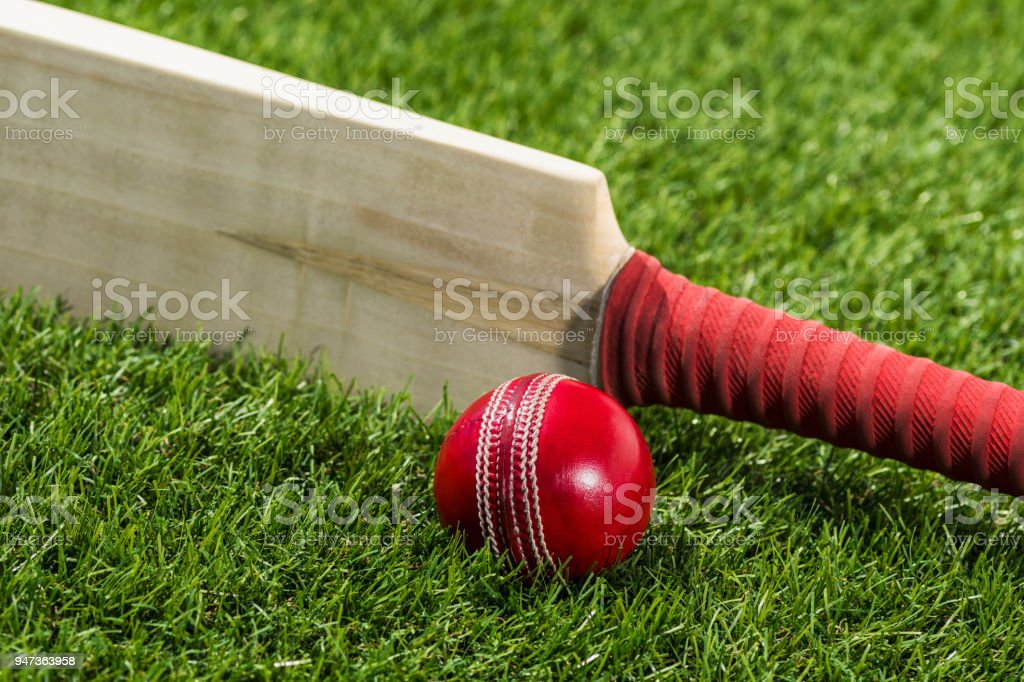 Looking down on a Cricket ball sitting in the grass with a bat on edge stock photo