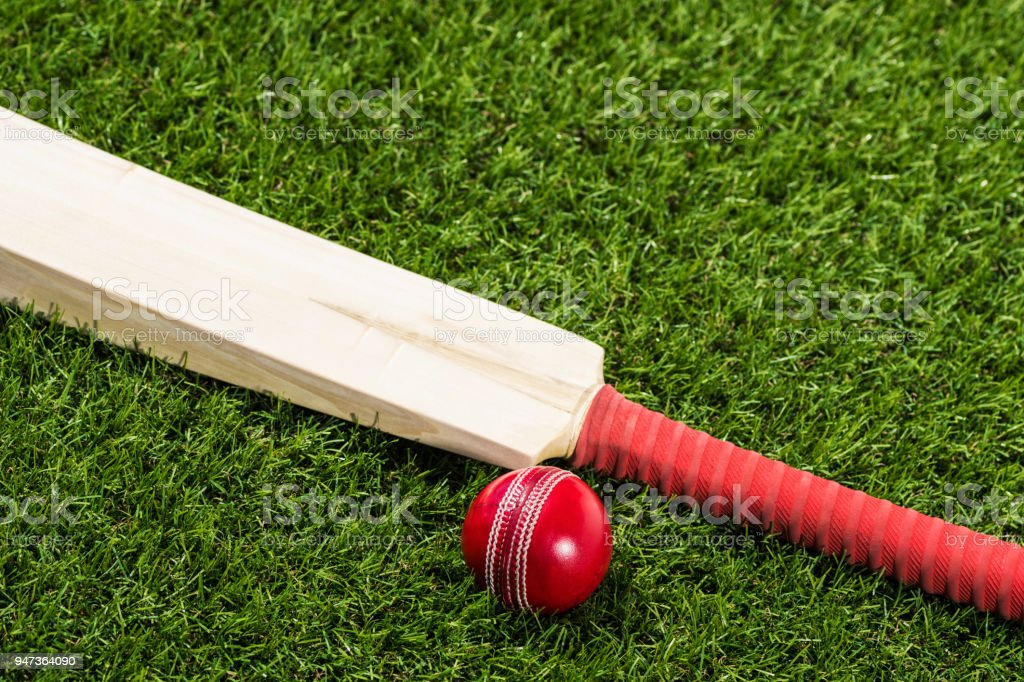 Looking down on a Cricket ball sitting in the grass with a bat stock photo