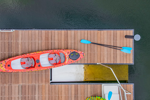 Looking down on a dock in the water with a kayack and paddles and life vests beside a kayac lanching platform