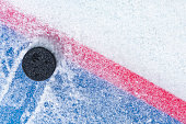 """Looking down on a black ice hockey puck plowing through snow and stopping on the edge of the """"Goal Line"""" of the goal crease.  The puck must cross completely over the red line to count as a goal."""