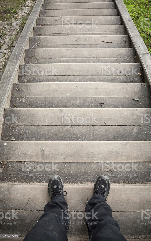 Looking down on a male legs and wooden stairway stock photo