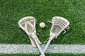 Looking down on a pair of Lacrosse sticks and a white ball sitting on the white Midfield-line of an artificial turf sports field.
