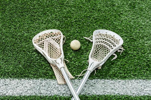 looking down on a pair of lacrosse sticks and a ball on the midfield-line - lacrosse zdjęcia i obrazy z banku zdjęć