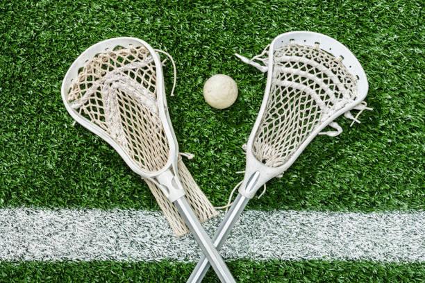 looking down on a pair of lacrosse sticks and a ball on the midfield-line - kij do gry w lacrosse zdjęcia i obrazy z banku zdjęć