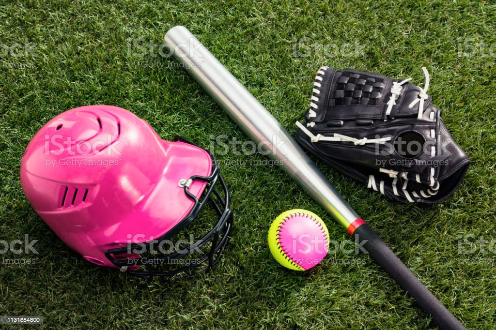 A high angle view of a pink and yellow softball along with an...