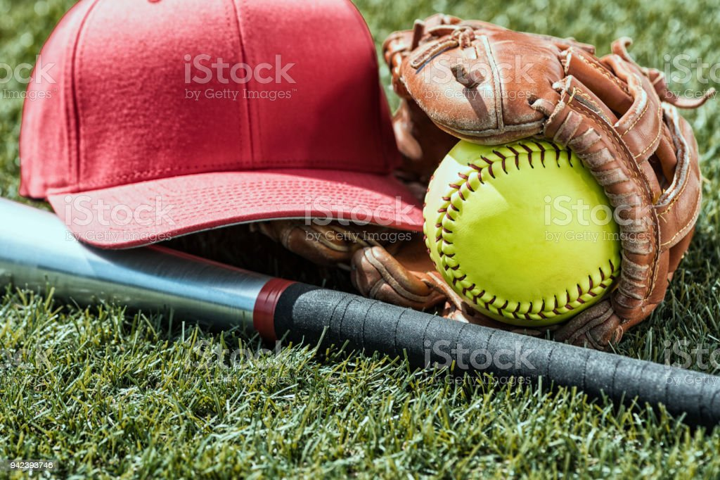 Looking down on a yellow softball in glove with a red cap and bat sitting in the grass - Grunge look stock photo