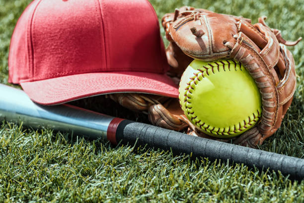 looking down on a yellow softball in glove with a red cap and bat sitting in the grass - grunge look - softball stock photos and pictures