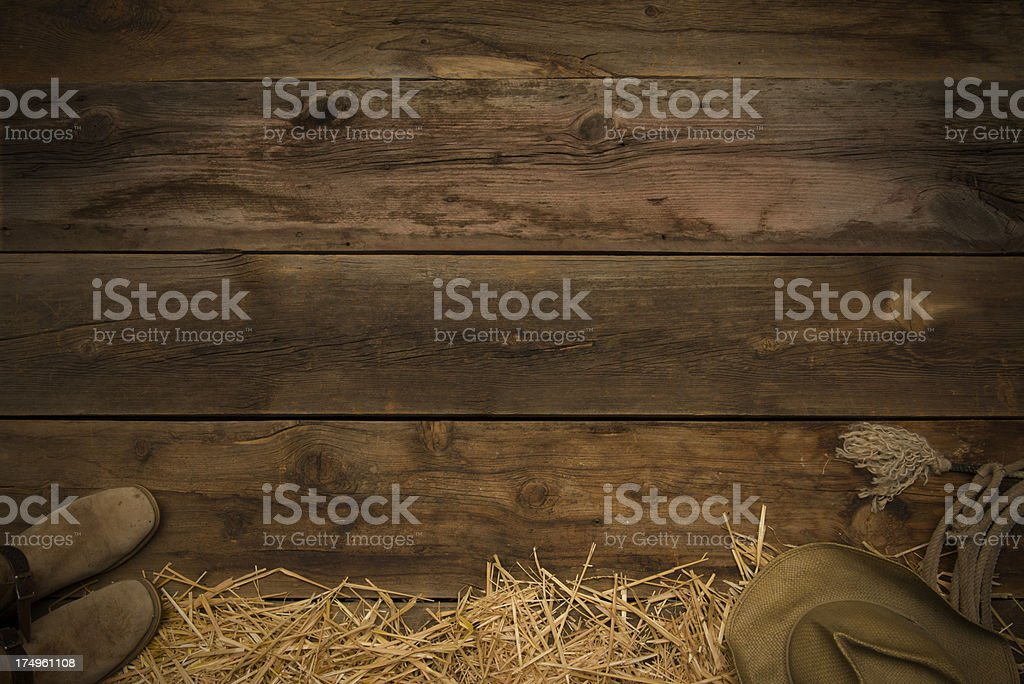 Looking down on barn floor-cowboy hat,boots,rope and hay stock photo