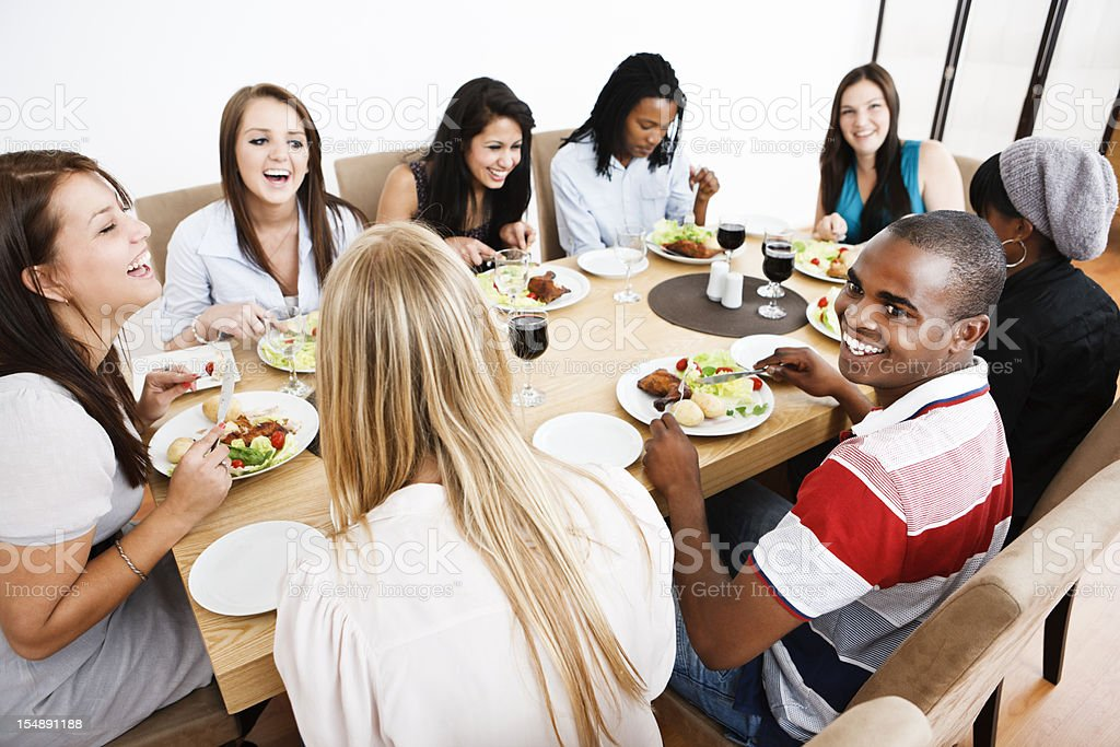 Looking down on happy, laughing friends round dining table royalty-free stock photo