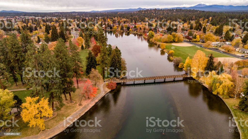 Looking down on Mirror Pond on the Deschutes River in Bend Oregon lined with autumn colored trees stock photo