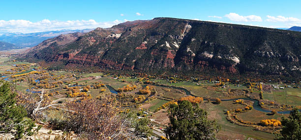 Looking down on the Animas river valley in the fall Taken from the Animas Mountain Trail in Durango, CO.   The winding Animas river curves through the valley, dotted with bright yellow deciduous trees changing in the autumn.  A large, red hill lines the opposite side of the valley.  Homes, fields and farms run throughout the fertile valley. animas river stock pictures, royalty-free photos & images