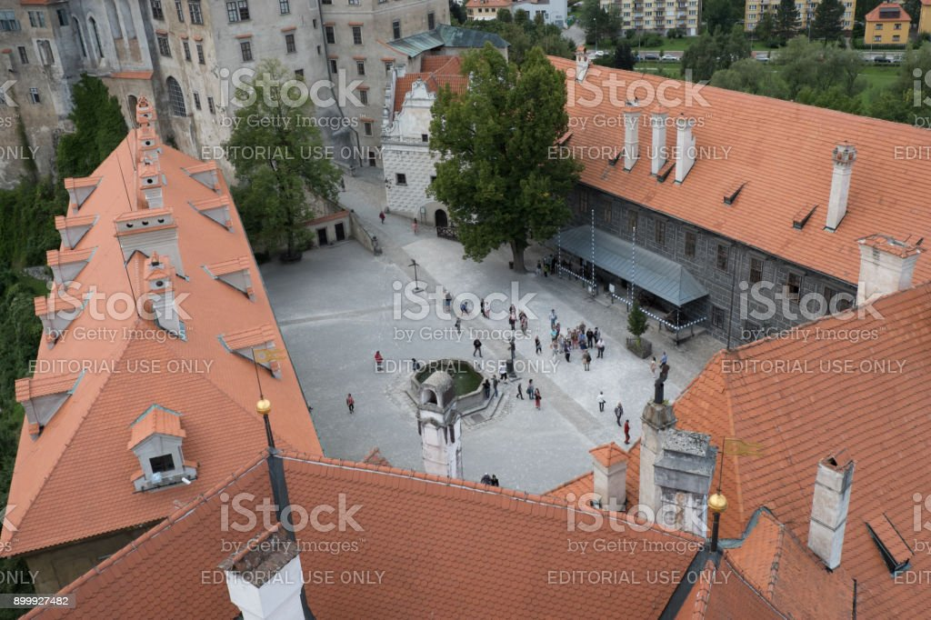 Looking down on the second courtyard of Cesky Krumlov Castle, people walking around the fountain in the courtyard, view from castle tower above. stock photo