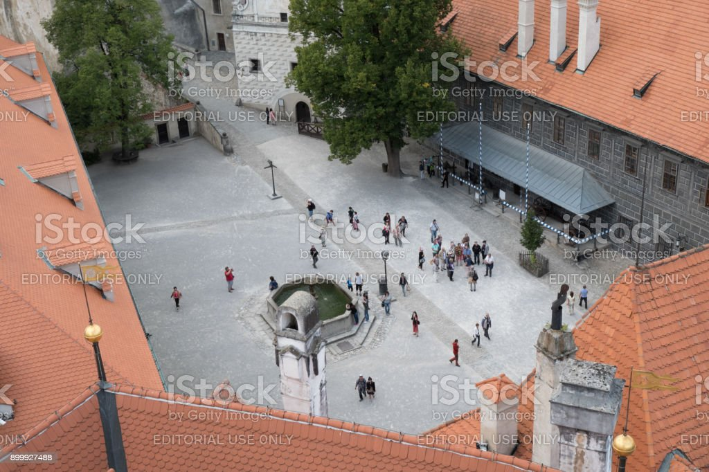 Looking down on the second courtyard of Cesky Krumlov Castle, people walking around the fountain in the courtyard, looking from castle tower down below. stock photo