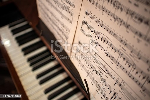 Looking down onto out of focus piano keys with sheet music in the forground
