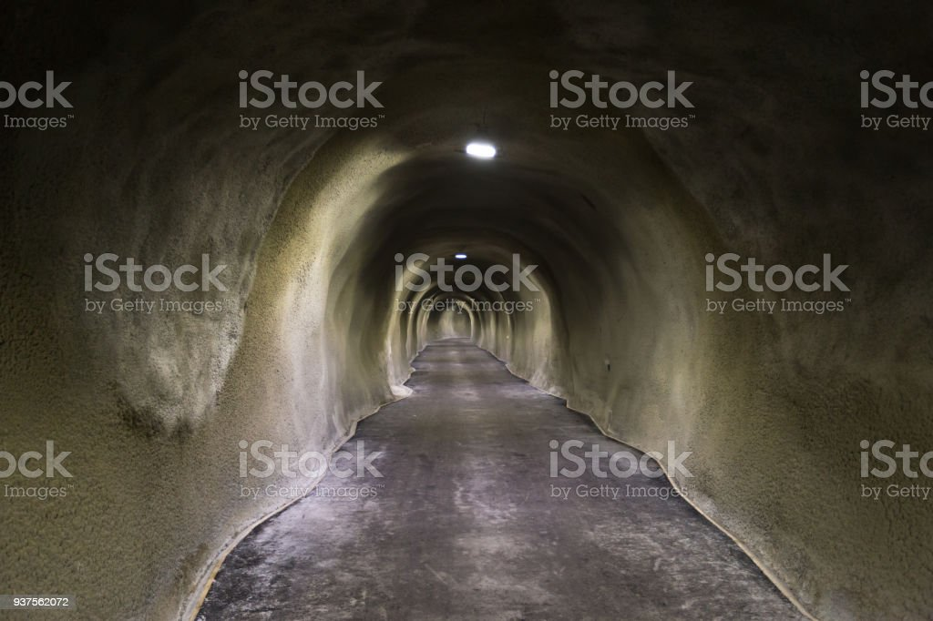 Looking down the barrel of a long concrete snow tunnel stock photo