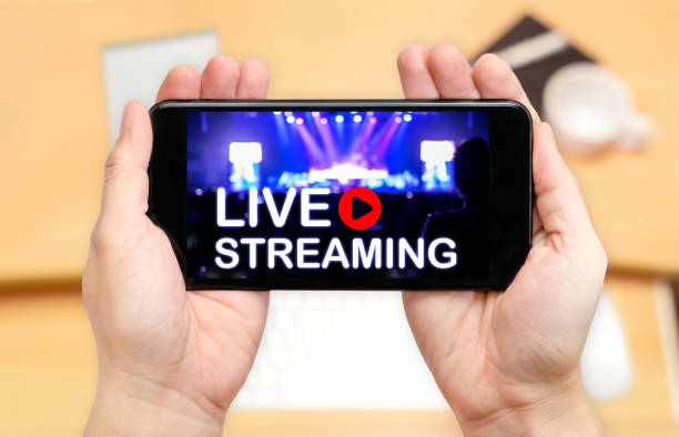 looking down to see two hand holding mobile phone with live streaming word on screen and blur desk office background,video marketing concept - free images for downloads stock photos and pictures