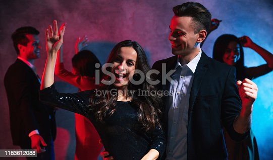 497317250 istock photo Looking fancy. Gorgeous woman with curly hair is dancing with her right hand up, while her boyfriend is hugging and looking at her with love, dancing at the club, surrounded with their friends. 1183612088