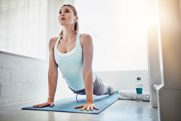 Looking for a healthier way to start your day? Shot of a woman practising the cobra pose at home upward facing dog position stock pictures, royalty-free photos & images
