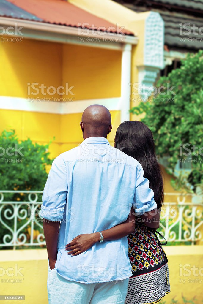 Looking for a new home African couple looking at their new house, back view. Adult Stock Photo