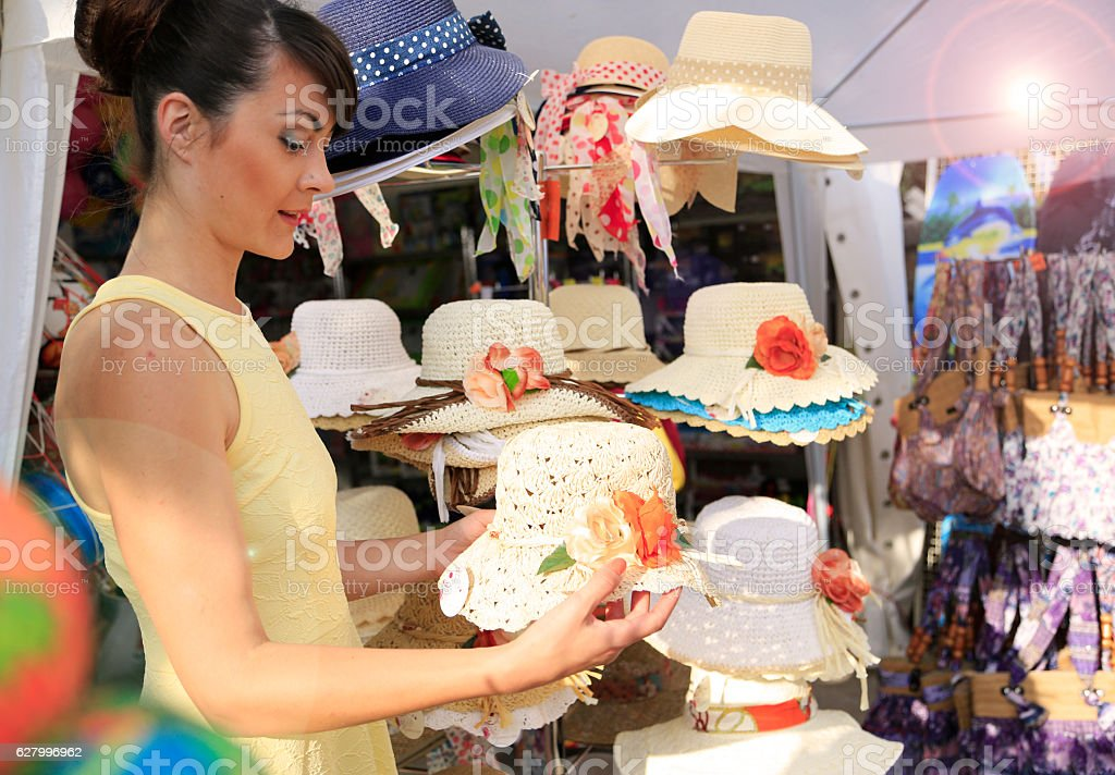 Looking for a straw hat on a street market stock photo