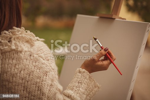 Over the shoulder view of an empty artist's canvas. Female artist is holding a paintbrush, ready to start working.