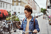 Shot of an attractive young woman using her cellphone while out cycling through the city