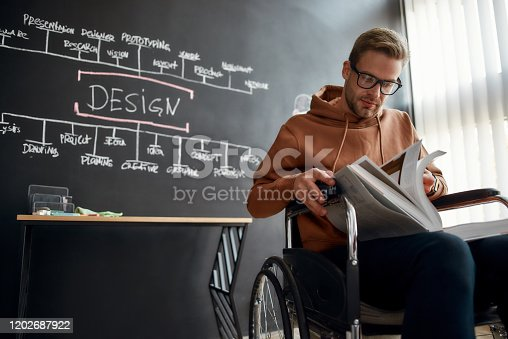 Concentrated young designer or architect in a wheelchair reading book while sitting near blackboard with presentation in the creative office. Disability concept. Study concept. Web design