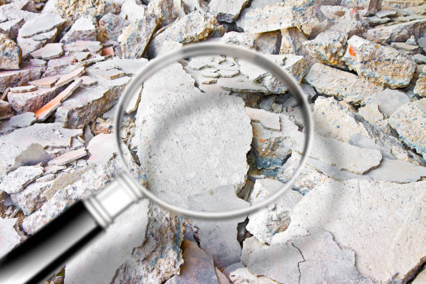 Looking for danger asbestos particles in industrial waste after demolishing a concrete wall - Concept image seen through a magnifying glass stock photo