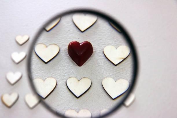 Auf der Suche nach verschiedenen Herzen zwischen den Haufen von gleichen Holzherzen – Foto