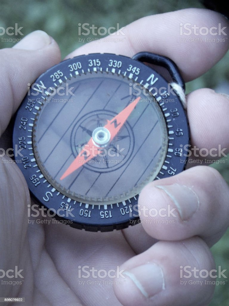 Looking for Direction on Which Way to Go with a Very Problematic Compass in my Hand with 2 Letter N's showing Magnetic North on Both Sides of the Red Arrow stock photo