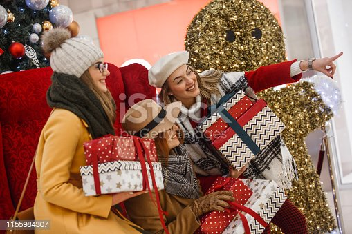 Three women are sitting in an armchair, holding Christmas gifts and looking at shop window at the mall.