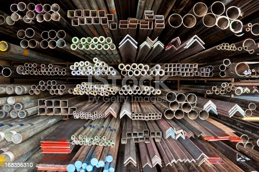 Various angle iron profiles and steel rods kept in storage shelves in a steel shop.
