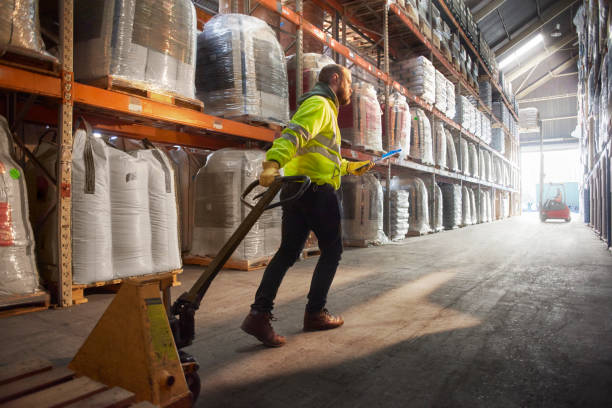 looking for the right pallet a warehouse worker walks down the aisle of stock pulling the stacker trolley behind him pallet jack stock pictures, royalty-free photos & images