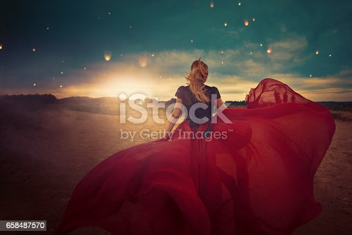 rear view of young woman with red dress flying in the wind, enjoying freedom, nature and the beauty of sunset.