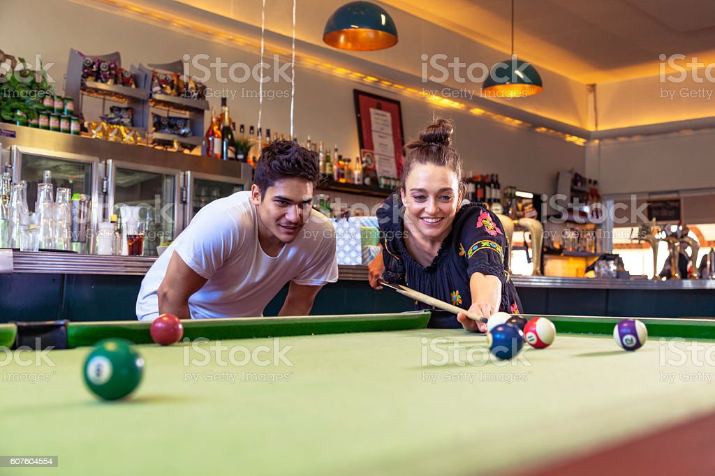 Looking good: guy helps girl with pub pool table shot stock photo