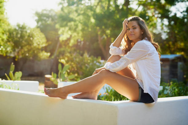 Looking good in the summer sun Portrait of an attractive young woman sitting outdoors shorts stock pictures, royalty-free photos & images