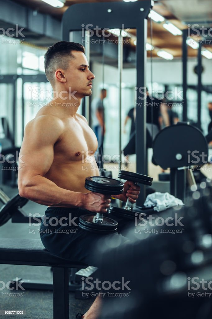 Shot of a young muscular man holding dumbbells at a gym