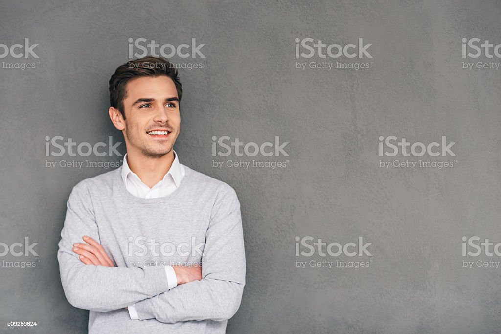 Looking in future with smile. Confident young man keeping arms crossed and looking away with smile while standing against grey background 20-29 Years Stock Photo
