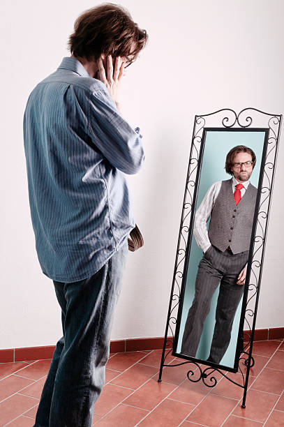 Looking into the mirror to find a better self Double self-portrait while hoping for better. Which one is real? One is not pleased! alias stock pictures, royalty-free photos & images