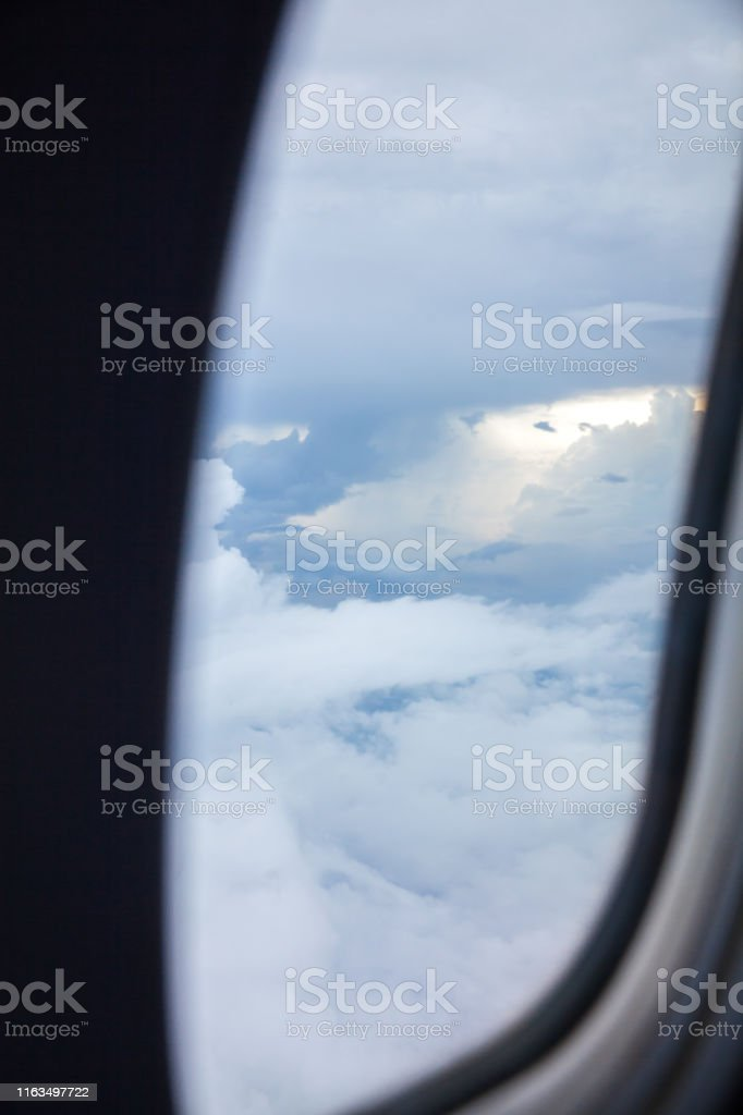 Looking majestic sea of clouds through airplane window