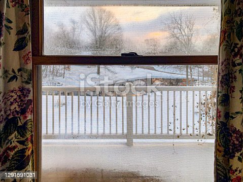 Looking out the screened window onto a snowy scene. Curtains frame the image