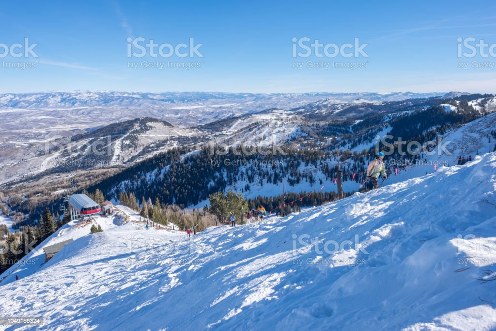 Looking out from a mountain peak - skiers hiking up the mountain stock photo