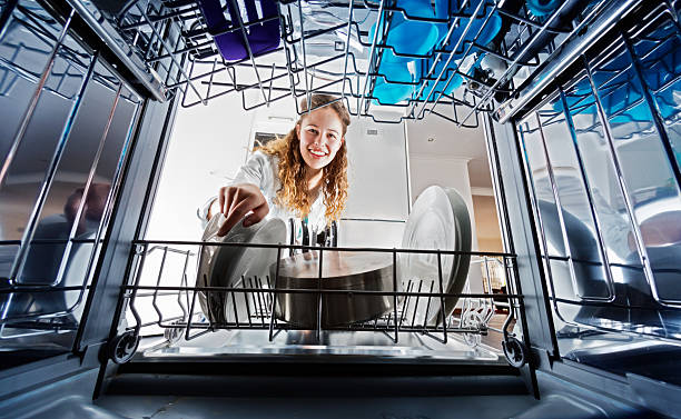 Looking out from dishwasher interior at young woman loading dishes A smiling young woman seen, unusually, from inside the dishwasher drum, loads or unloads dishes. dishwasher stock pictures, royalty-free photos & images
