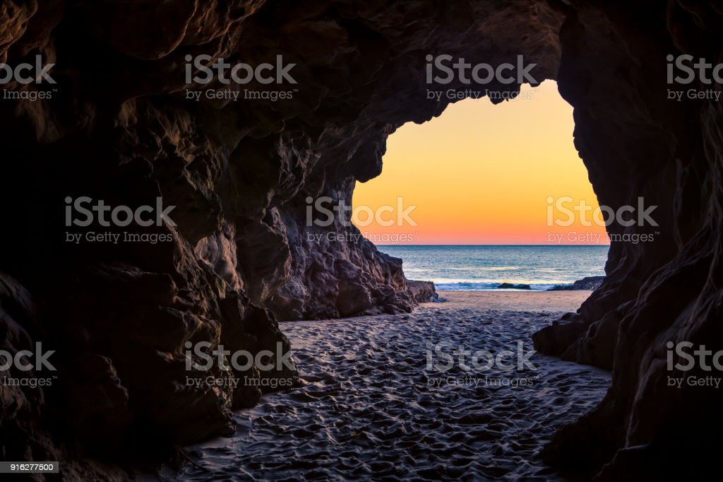 Looking out of a beach cave at sunset, Leo Carillo State Beach, California stock photo