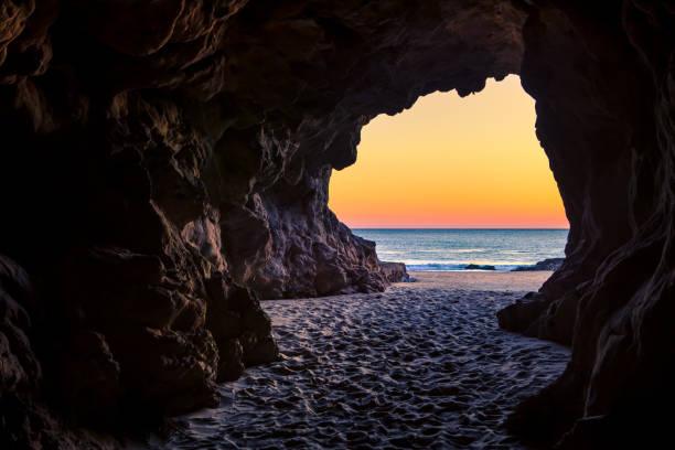 uit een grot strand kijken naar zonsondergang, leo carillo state beach, californië - grot stockfoto's en -beelden