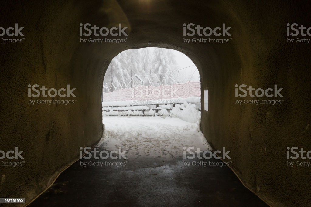 Looking out of a tunnel onto a ski run in snowbound Zermatt stock photo